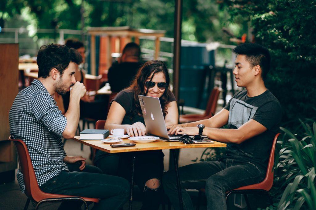 jovens em uma mesa conversando e tomando café