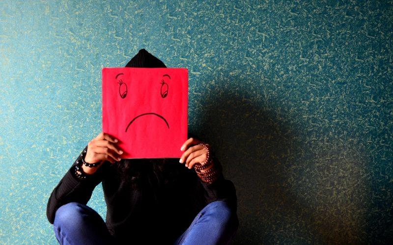 Homem com papel de desenho triste em frente ao rosto